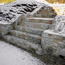 Kamenná zeď v zahradě se schodištěm